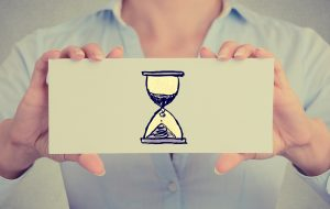 Time management productivity concept. Closeup businesswoman hands holding white card sign with sand clock sign isolated on grey wall office background. Retro instagram style image